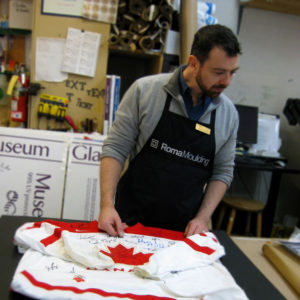 Custom Framer Nick Csernak is folding the Team Canada Hockey Jersey before sewing it down to a mat board.